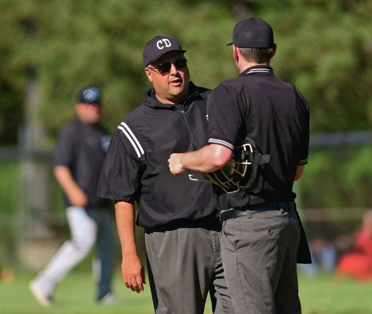 Base umpire Greg Massaroni, left, is seen talking to home plate umpire Sean Ellott during a baseball game between Colonie and Columbia at Cook Park on Thursday, June 10, 2021 in Colonie, N.Y. (Lori Van Buren/Times Union)