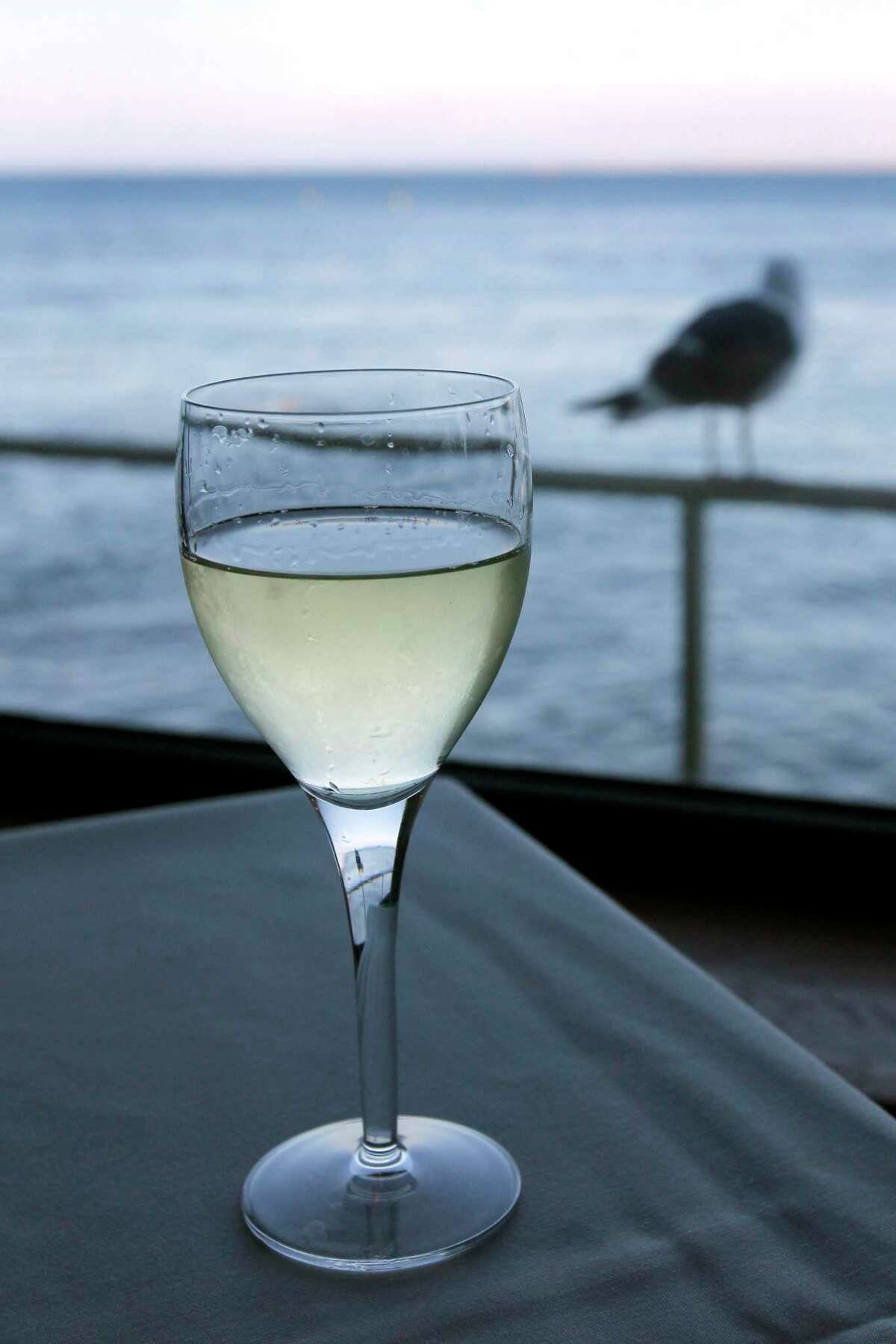 A glass of chilled white wine at the beach. Chilled wine makes a refreshing treat on Father's Day.