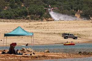 A CalFire helicopter practices water drops along Folsom Lake in Granite Bay, Calif., on June 16, 2021.