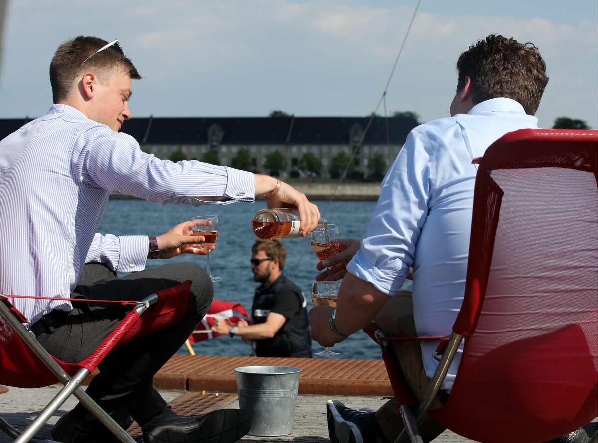 Two men drinking wine at Ofelia Plads. (Photo by Anton Novoderezhkin\TASS via Getty Images)