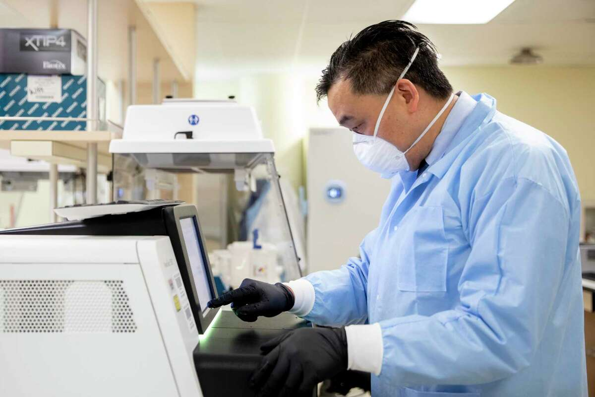 UCSF-Abbott Viral Diagnostics and Discovery Center lab director Dr. Charles Chiu demonstrates how to use the Illumina NextSeq550 sequencer used to read sequences of the COVID-19 virus in his lab in San Francisco, Calif. Tuesday, January 5, 2021. Public health experts are increasingly concerned about the impact of highly contagious coronavirus variants. UCSF is running tests on the strains of the virus circulating in California to help identify new strains.