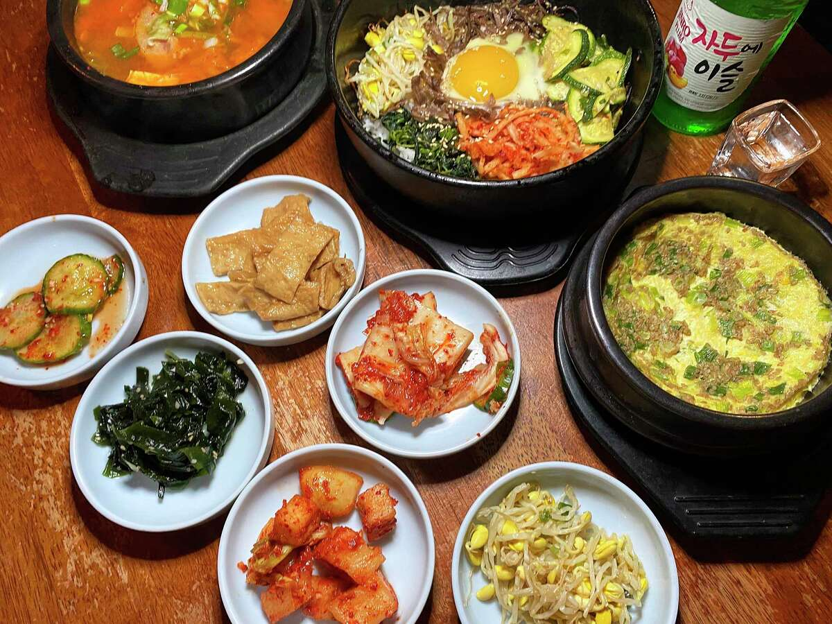 The late-night possibilities at Arirang include, clockwise from top left, kimchi stew, dolsot bibimbap, the Korean rice alcohol soju, steamed egg and an array of side dishes called banchan.
