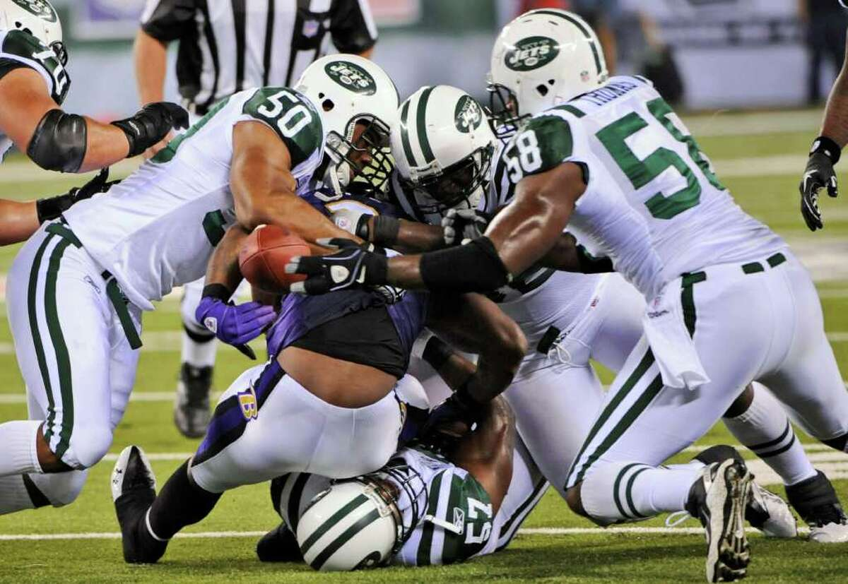 Baltimore Ravens running back Willis McGahee fumbles the ball as he is tackled by New York Jets' Vernon Gholston (50), Bryan Thomas (58) and others during the second quarter of an NFL football game at New Meadowlands Stadium in East Rutherford, N.J., Monday, Sept. 13, 2010. The Jets recovered the ball. (AP Photo/Bill Kostroun)