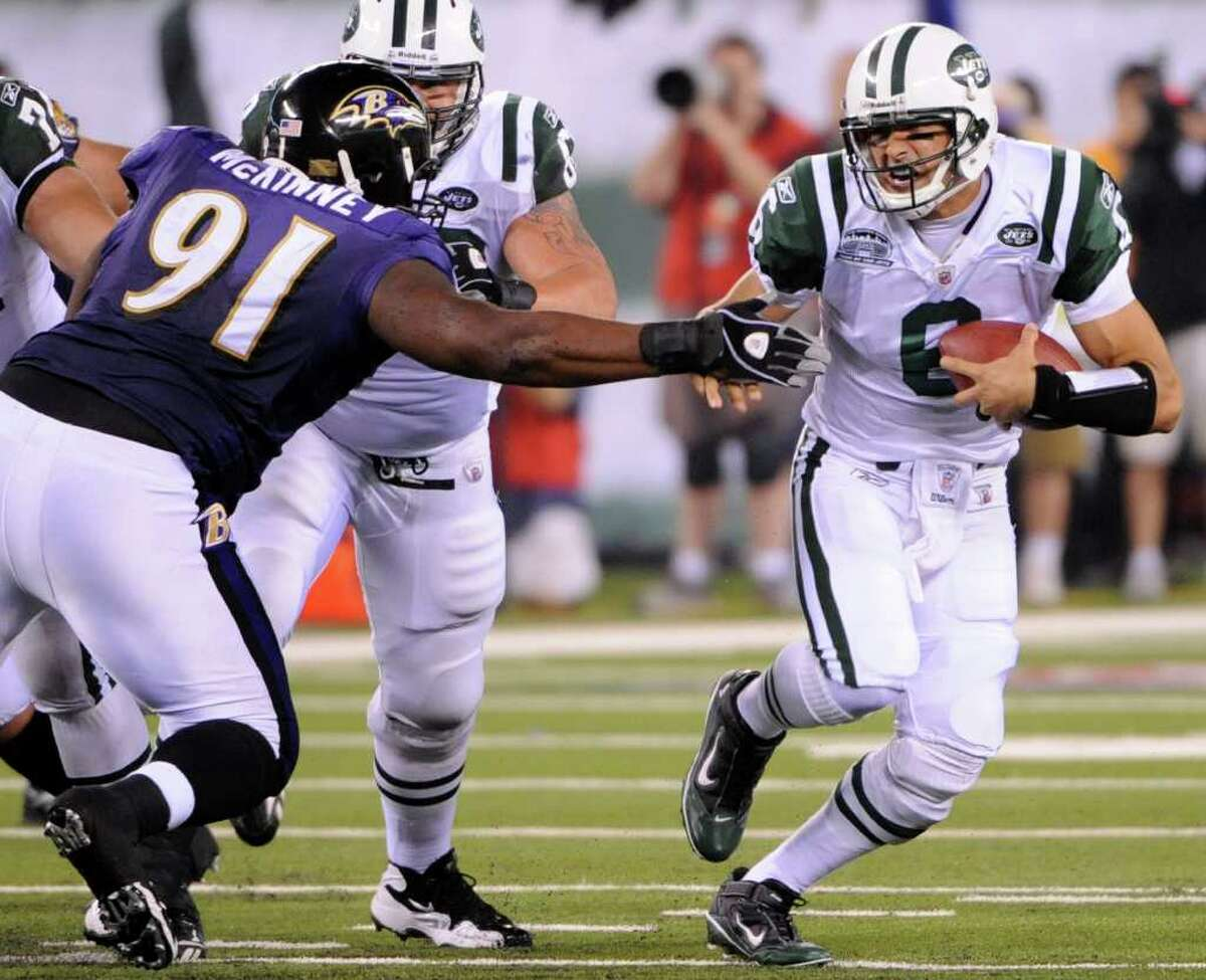 New York Jets quarterback Mark Sanchez (6) scrambles away from Baltimore Ravens' Brandon McKinney (91) during the third quarter of an NFL football game at New Meadowlands Stadium in East Rutherford, N.J., Monday, Sept. 13, 2010. The Ravens won 10-9. (AP Photo/Bill Kostroun)