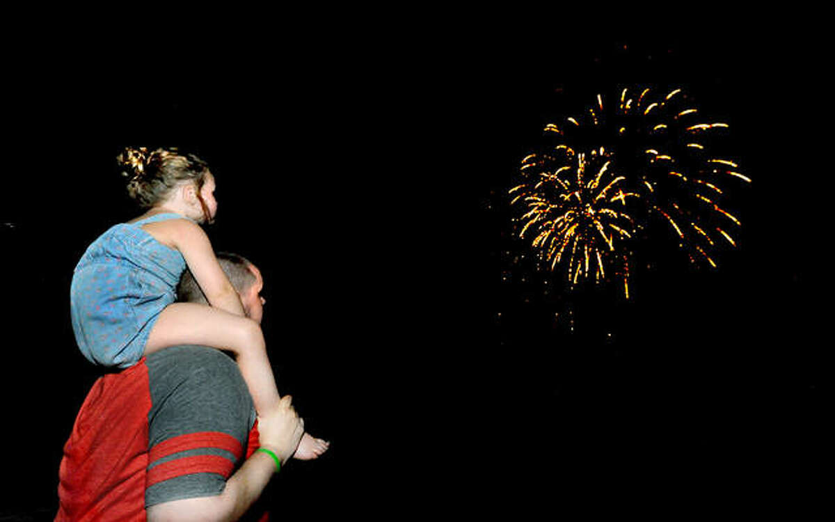 In this July 2020 file photo, Richard Miller and his daughter Zoey, 4, of Collinsville, watch fireworks at Edwardsville High School.
