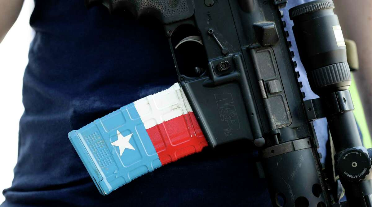 The ammo magazine is made to look like the Texas flag as gun rights advocates gather outside the Texas Capitol where Texas Gov. Greg Abbott held a round table discussion, Thursday, Aug. 22, 2019, in Austin, Texas. Abbott is meeting in Austin with officials from Google, Twitter and Facebook as well as officials from the FBI and state lawmakers to discuss ways of combatting extremism in light of the recent mass shooting in El Paso that reportedly targeted Mexicans. (AP Photo/Eric Gay)
