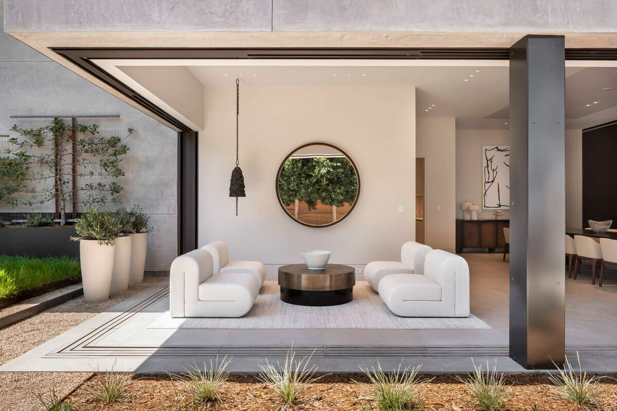 This lounge area looks out at a rear garden with stone hardscape, fire pit, lawn and outdoor kitchen.