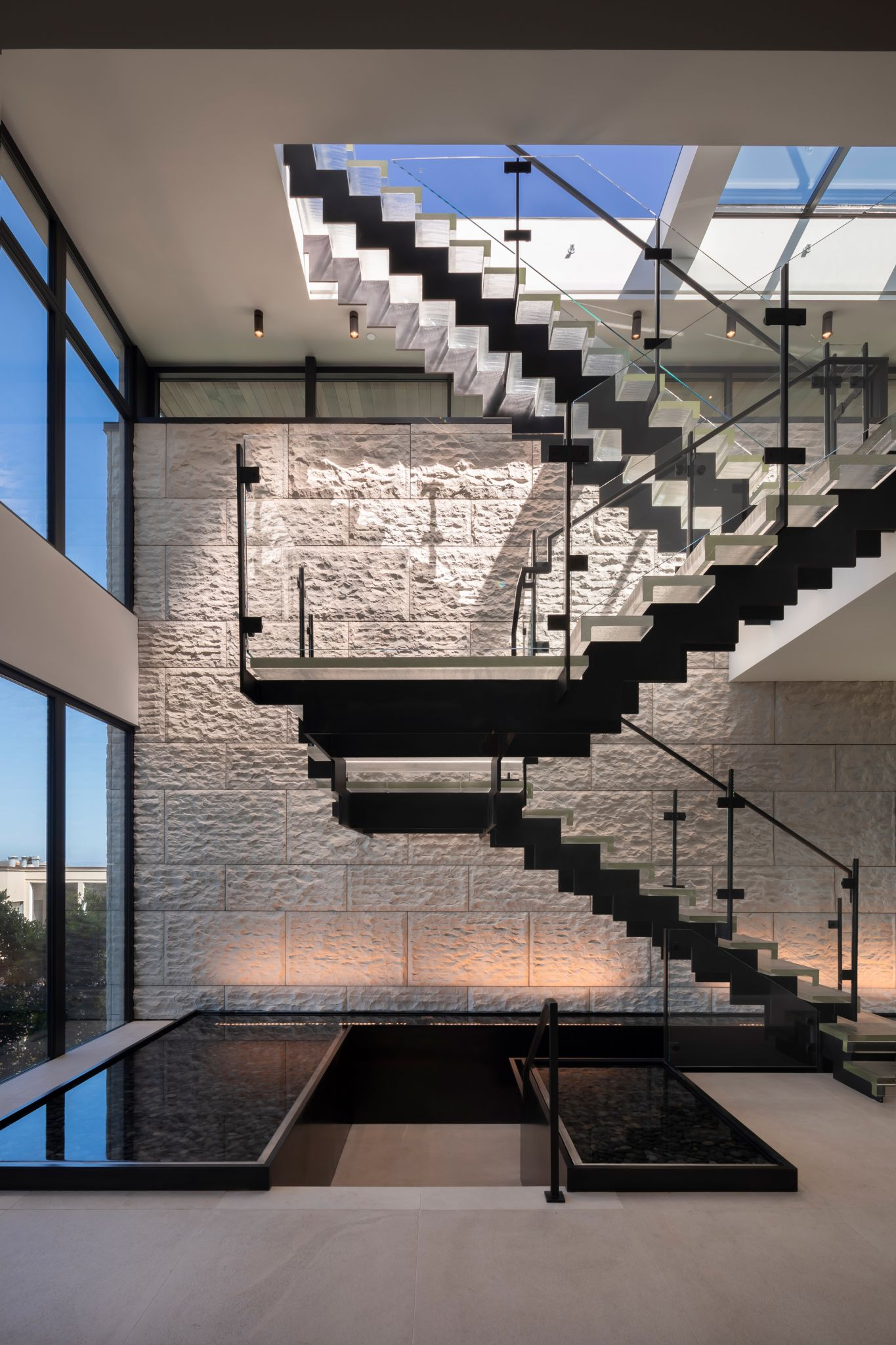 The home has a high-speed elevator, but this floating glass staircase, rising up over indoor reflecting pools toward a massive operable skylight, is art.