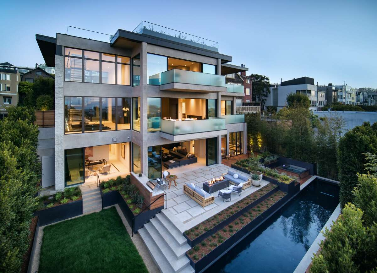 This view from the backside of the newly constructed home highlights the seamless indoor/outdoor flow of its design.