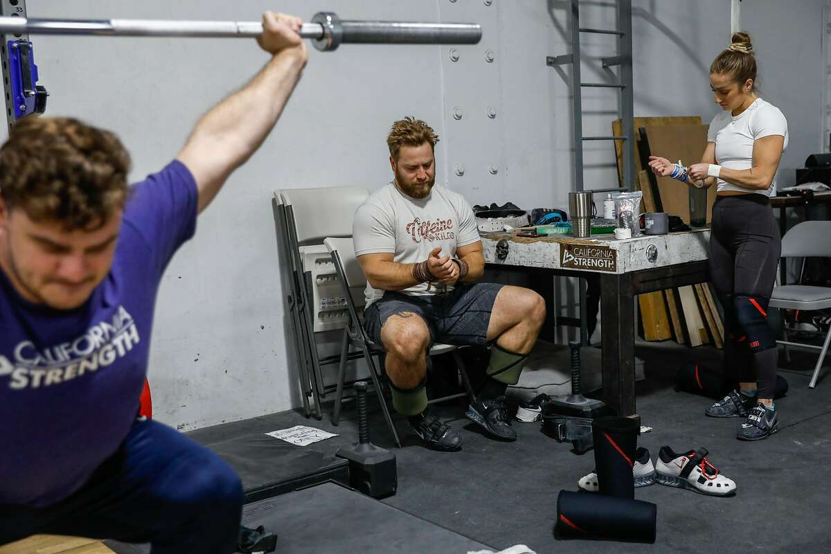 American weightlifter Wes Kitts (center), a Tennessee native who moved to California gets wrist supports on before a workout at California Strength on Thursday, June 10, 2021 in San Ramon, California. He has qualified for the Tokyo Olympics.