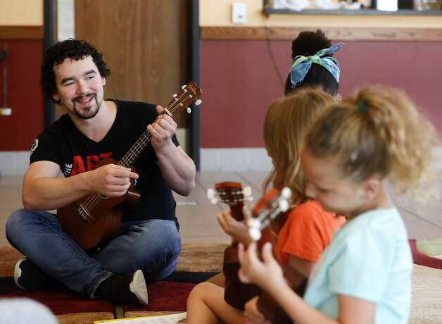 Instructor Zachary Stallings encourages a student for her correct finger position while playing a ukulele during the Multi-Arts Camp at the Owen Theatre, Thursday, June 17, 2021, in Conroe. Area volunteers taught twenty-one students at the week-long camp the fundamentals of art, acting and music. Photo: Jason Fochtman/Staff Photographer / 2021 ? Houston Chronicle
