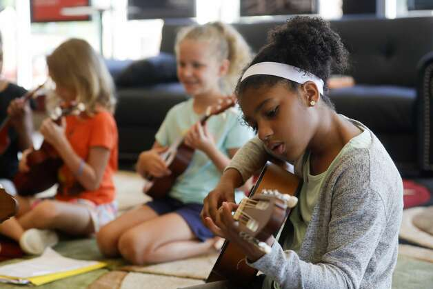 """Victoriya Houston checks her chord position as she practices 'This Land is Your Land"""" by Woody Guthrie during the Multi-Arts Camp at the Owen Theatre, Thursday, June 17, 2021, in Conroe. Area volunteers taught twenty-one students at the week-long camp the fundamentals of art, acting and music. Photo: Jason Fochtman/Staff Photographer / 2021 ? Houston Chronicle"""