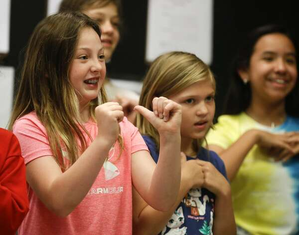 """Addison Lloyd, left, performs hand motions while singing """"This Land is Your Land"""" by Woody Guthrie during the Multi-Arts Camp at the Owen Theatre, Thursday, June 17, 2021, in Conroe. Area volunteers taught twenty-one students at the week-long camp the fundamentals of art, acting and music. Photo: Jason Fochtman/Staff Photographer / 2021 ? Houston Chronicle"""