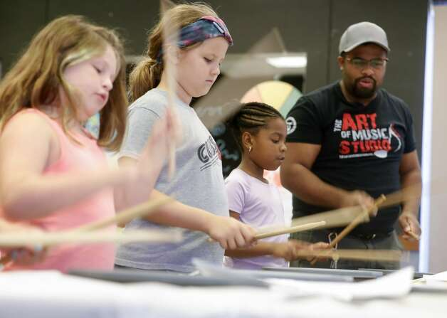 """Jourdyn Mackey, second from right, works on her drumming of """"This Land is Your Land"""" by Woody Guthrie during the Multi-Arts Camp at the Owen Theatre, Thursday, June 17, 2021, in Conroe. Area volunteers taught twenty-one students at the week-long camp the fundamentals of art, acting and music. Photo: Jason Fochtman/Staff Photographer / 2021 ? Houston Chronicle"""