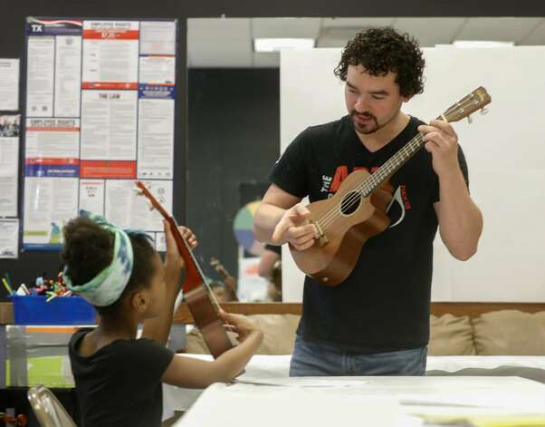 Instructor Zachary Stallings checks a student's finger position while playing a ukulele during the Multi-Arts Camp at the Owen Theatre, Thursday, June 17, 2021, in Conroe. Area volunteers taught twenty-one students at the week-long camp the fundamentals of art, acting and music. Photo: Jason Fochtman/Staff Photographer / 2021 ? Houston Chronicle