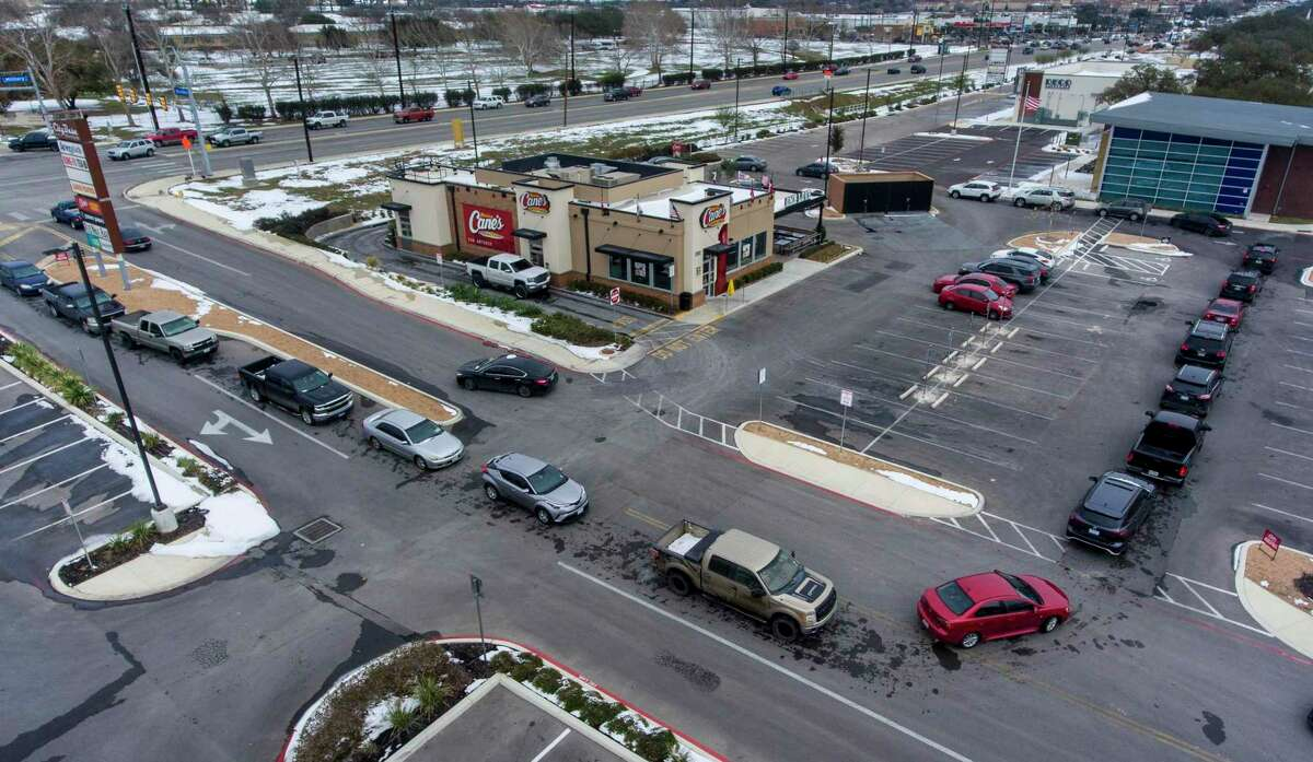 FILE: Vehicles encircle a Raising Cane's Chicken Fingers restaurant during Winter Storm Uri, Tuesday, Feb. 16, 2021 on SE Military Dr. near S. Presa St.