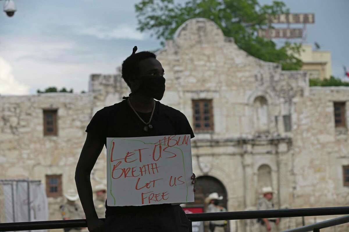 Isaiah Adams holds a sign in front of the Alamo on May 31, 2020, during a peaceful demonstration following the death of George Floyd.