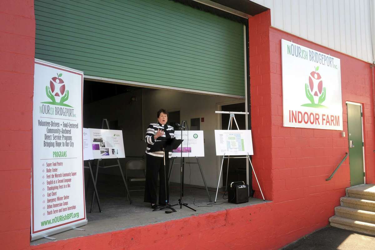 Rev. Sara Smith, founder and CEO of nOURish BRIDGEPORT, speaks from the loading dock of the non-profit's new location during a ribbon cutting ceremony in Stratford, Conn. June 16, 2021. The building will soon be converted indoor vertical hydroponic farm.