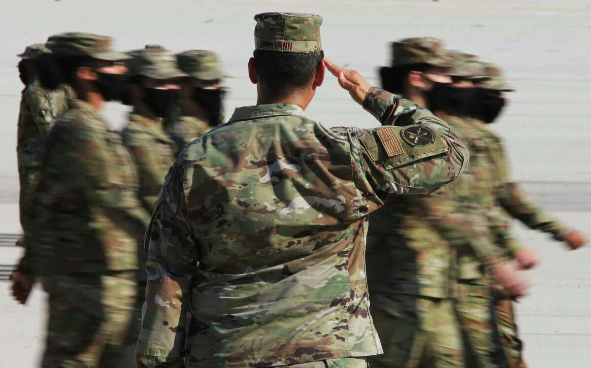 Lt. Col. Raymond Vann returns a salute as new airmen march past. JBSA-Lackland conducted its first pass-and-review ceremony in 15 months Thursday.