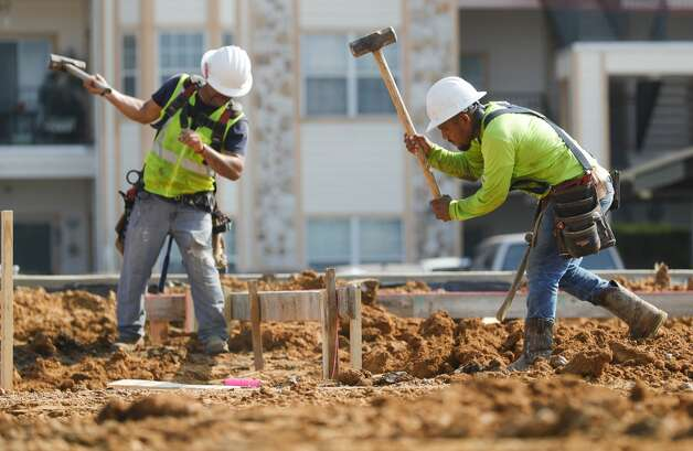 Construction workers use sledgehammers to drive wooden stakes for the perimeter of a buildingÕs foundation along Texas 105, Tuesday, June 15, 2021, in Montgomery. Heat indexes eclipsed 100 degrees Tuesday with the heat wave expected to continue through the week. Photo: Jason Fochtman/Staff Photographer / 2021 ? Houston Chronicle
