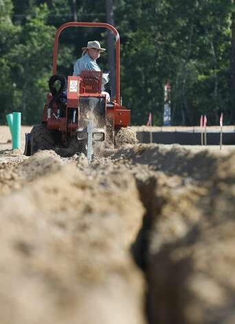 Barry Corley looks back at his trench as he digs his portion of a 4,000-foot gas line for new homes in the Granger Pines subdivision, Tuesday, June 16, 2021, in Grangerland. ÒThis time of year weÕre melting and itÕs not pretty,Ó Corley said noting he adds another 20 degrees to the outside temperatures from the hot engine air blowing on him. ÒIf it gets to 104-107 [degrees] with the heat index, weÕll just call it off for the day. ItÕs not worth someone getting hurt, itÕs just work. It will be here tomorrow.Ó Photo: Jason Fochtman/Staff Photographer / 2021 ? Houston Chronicle