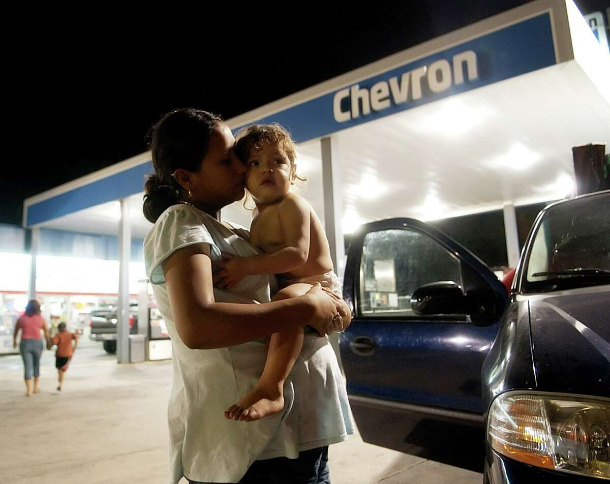 Heidi Delangel holds close her 1-year-old sister Mayline Guerro at a gas station just off of Interstate 10 in Lake Charles, La., early Friday, Sept. 23, 2005. They, along with other family members, try to decide where to go with what little gas they have. The family left Houston in hopes of evacuating to Alabama, as Hurricane Rita draws near. Delangel is 7 1/2 months pregnant. (AP Photo/The Austin American-Statesman, Matt Rourke) **NO MAGS, NO SALES, NO TV, INTERNET: AP MEMBERS, NEWSPAPERS ONLY**
