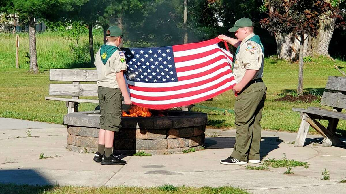 Boy Scout Troop 74 in Reed City burn retired flags during a ceremony on Flag Day, June 14. (Submitted photo)