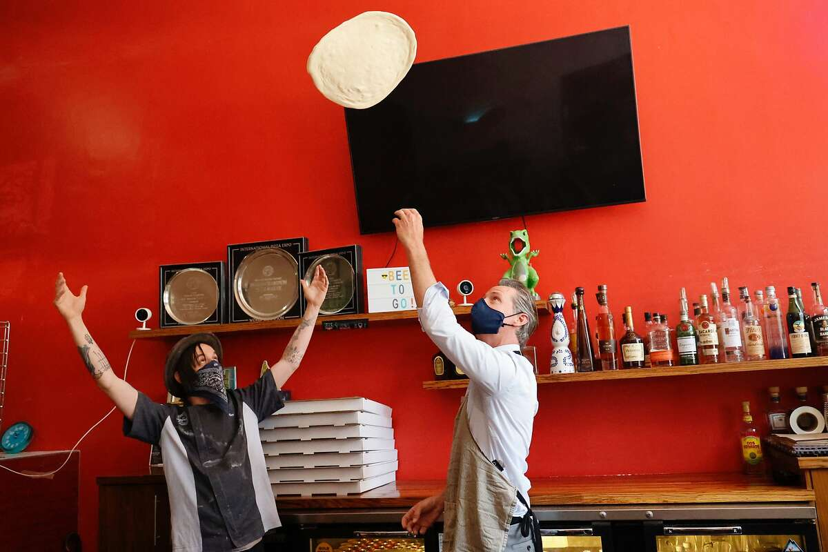Gov. Gavin Newsom is shown how to toss a pizza crust by Matt Molina, head chef at Graffiti Pizza. Small businesses are struggling to recover from the pandemic lockdown, which was finally lifted on June 15.