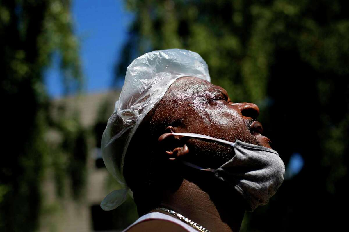 Christopher Fomby puts a plastic bag with some crushed ice on his head after leaving a Contra Costa County designated cooling center in Pleasant Hill.