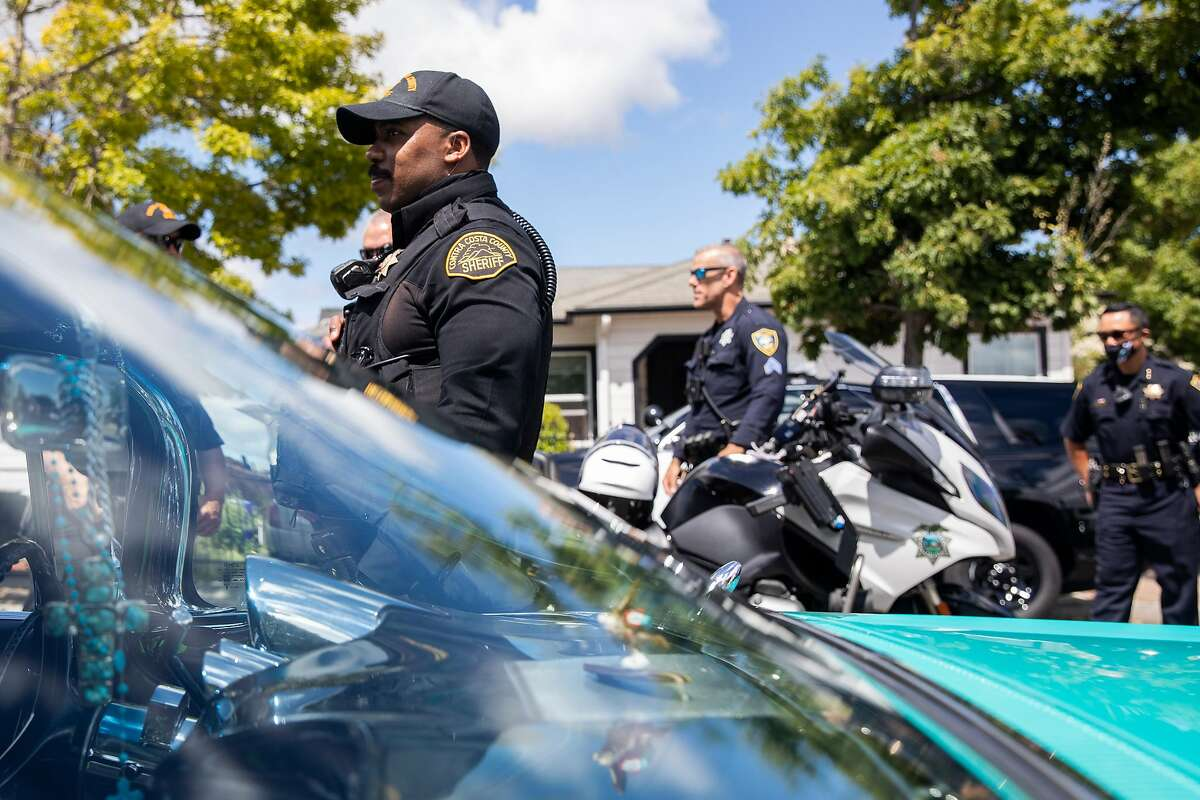 Richmond police officers, Contra Costa County sheriff's deputies, local community leaders and school board members prepare to head out on a walk through the Shields-Reid neighborhood to lobby against Police Department budget cuts.