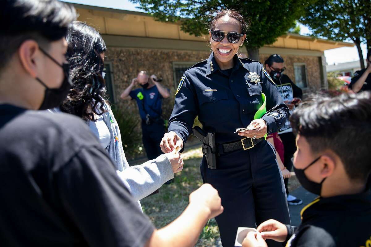 Richmond Police Chief Bisa French hands out stickers to schoolchildren outside Shields-Reid Community Center after an event to promote safe streets.