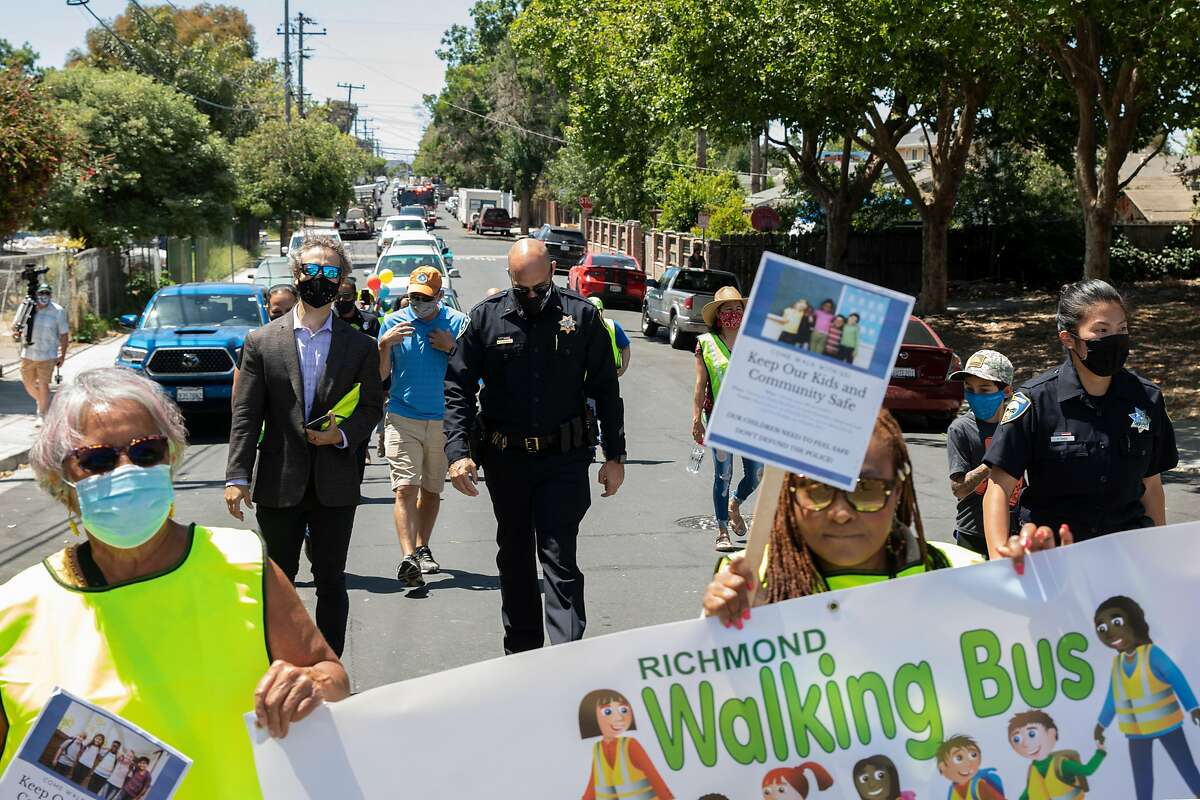 Richmond police officers, Contra Costa County sheriff's deputies, community leaders and school board members walk through the city's Shields-Reid neighborhood to promote safe streets.