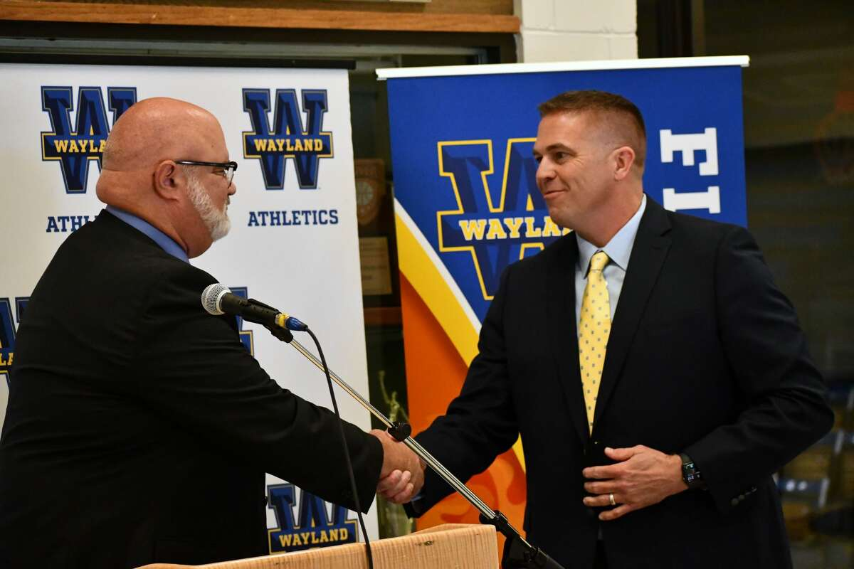 Jason Cooper (right) shakes the hand of Wayland Baptist Univerity's Senior Vice President of Operations and Student Life Claude Lusk after being introduced as the new head coach of the Wayland Baptist Flying Queens during a press conference on Thursday at the Hutcherson Center.