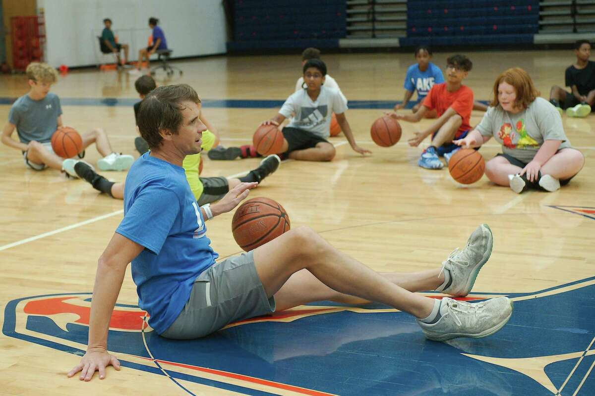 Clear Lake assistant basketball coach Matt Frye demonstrates a dribbling drill Thursday at the Clear Lake High School summer basketball camp.