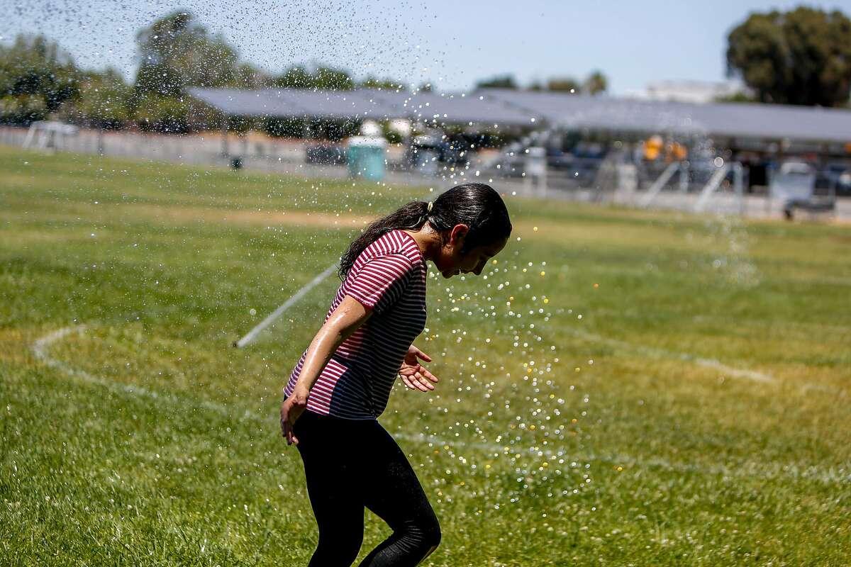 Estefania Ramirez, 13, plays in the sprinklers in a field in Pleasant Hill.