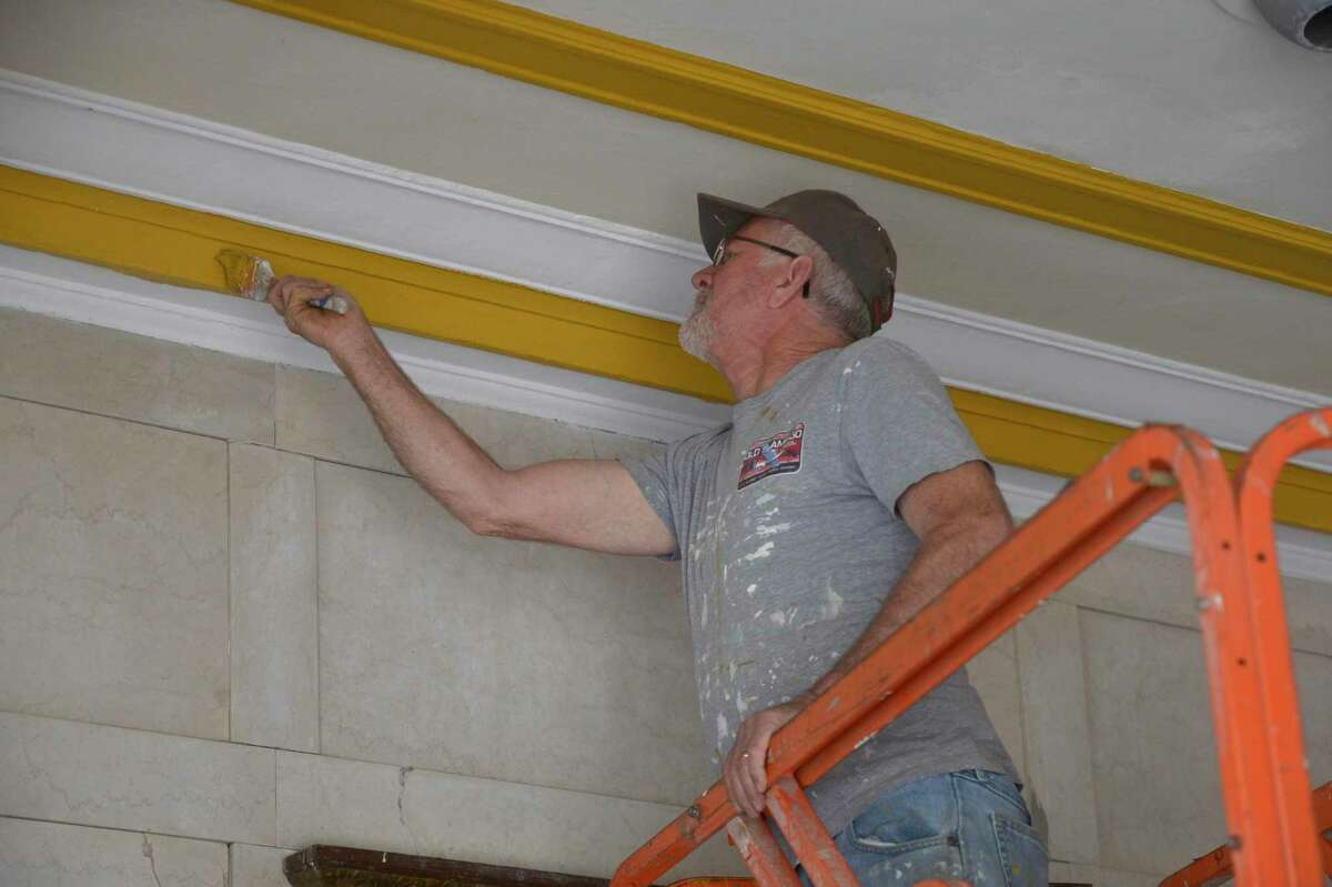 Alcindor DaSilva paints the ceiling of the entrance to Danbury's Palace theater Thursday. The downtown venue will reopen Saturday for the first time since March 2020. It is undergoing a minor restoration.