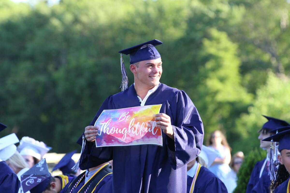 """The Morgan School Principal Keri Hagness gave messages to various members of the senior class to hold up during her speech to the class of 2021. Giuseppe Carpenter's sign says """"Be Thoughtful."""""""