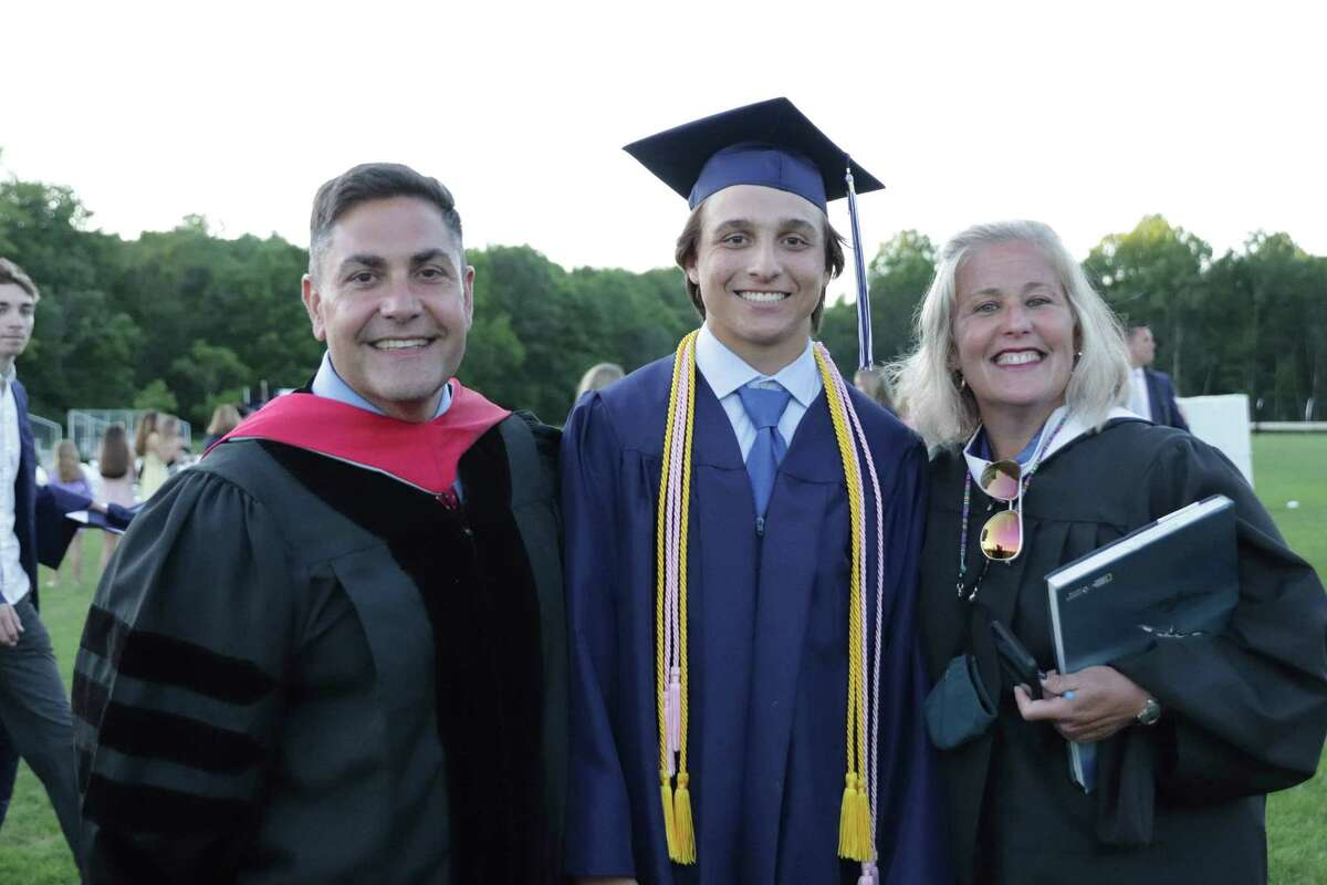 2021 Morgan School graduate Ryan Inglis poses with Chris Luther, assistant principal, and Laura Luther, Spanish teacher, at the graduation ceremony.