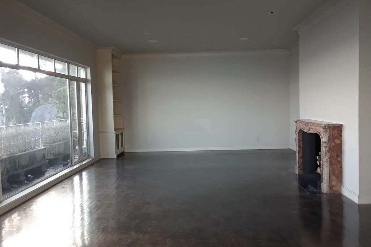 There are dark-stained hardwood floors throughout and a marble fireplace. A set of narrow stairs leads down to a separate living area and a small bedroom and bathroom.