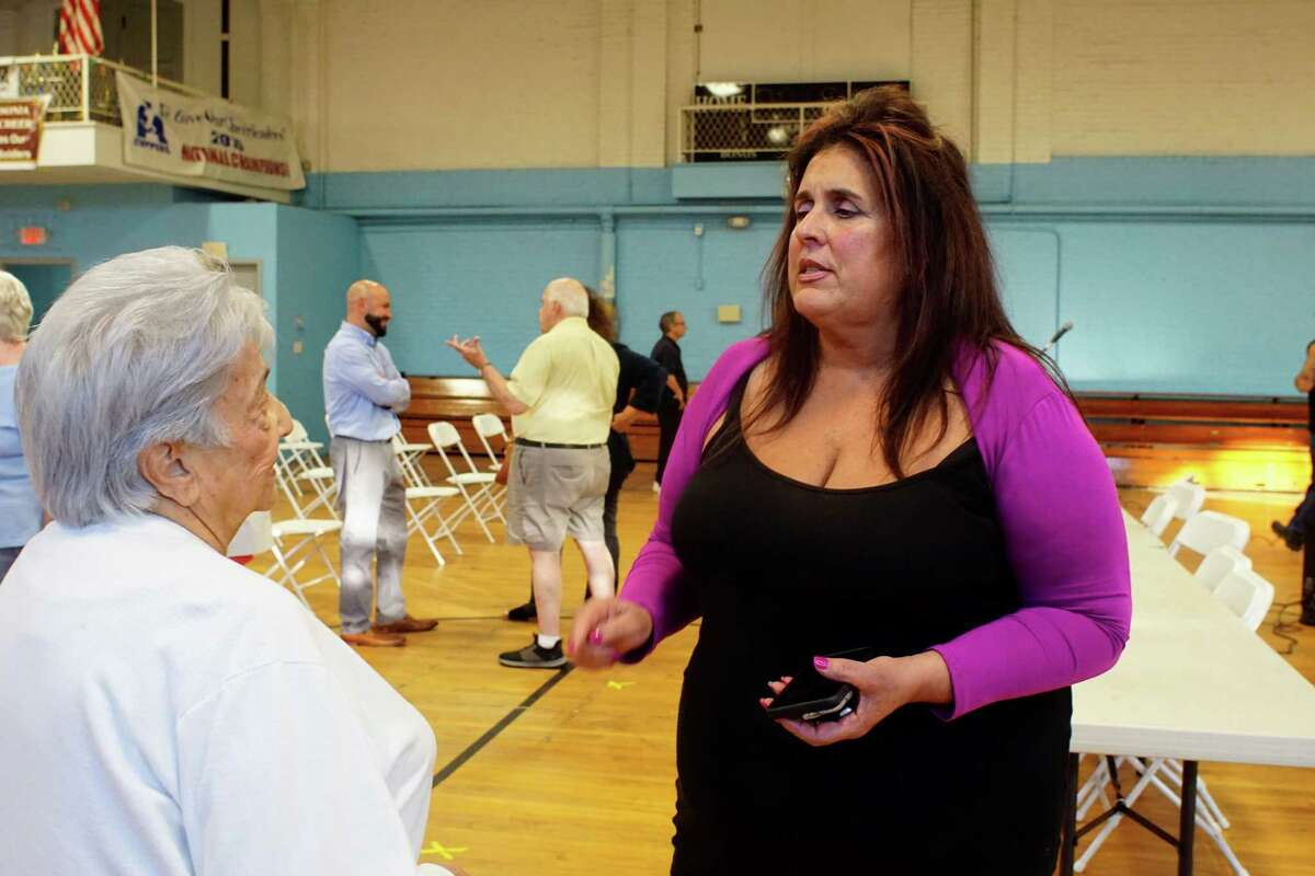 Sheila O'Malley, Ansonia's economic development director, speaks to a senior at a hearing at the Ansonia Armory on the proposed senior center that would be shared with Derby.