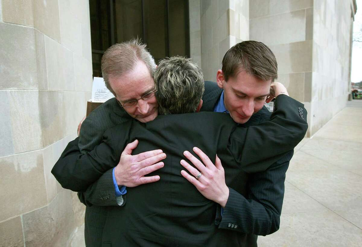DES MOINES, IA - APRIL 27: Gary Seronko (L) and his husband Curtis Rathmeier get a hug from Rev. Peg Esperanza following a brief wedding ceremony on the steps of the Polk County Administration Building in Des Moines, Iowa on April 27, 2009, the first day gay couples were allowed to marry in the state.