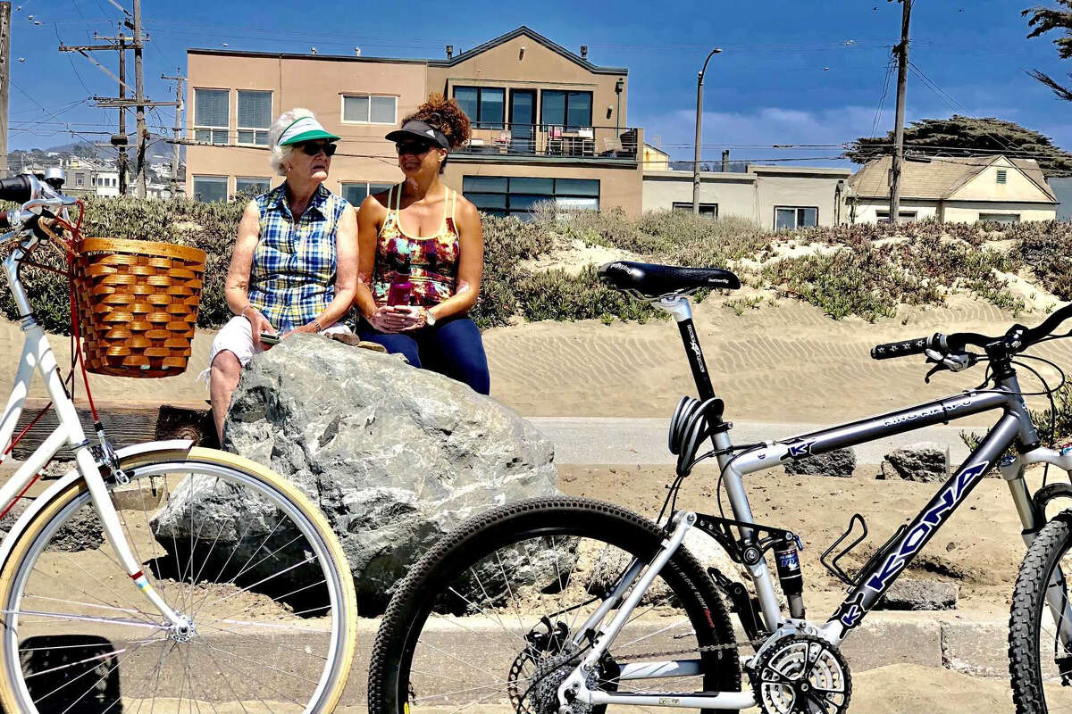 """Emma Bosch, left, and her daughter Pinder Baidwan bask in the sun on a break from bike riding at Ocean Beach this afternoon. Bosch arrived yesterday from Holland and says she """"couldn't have chosen a better time to visit."""""""