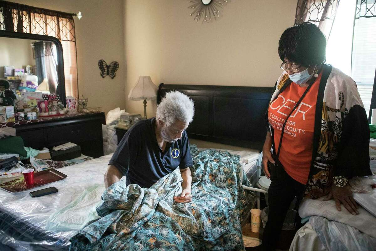 Delores McGruder, 72, checks in on her friend Ronald Ford, 69, who she takes care of in her home Wednesday, June 16, 2021 in Houston. Ford is bedridden and if the power should go out in the house, McGruder would have to take him to a hotel for his care.