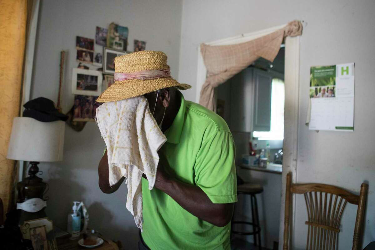 Feast Bennemie, 77, wipes away sweat in the living room of his Fifth Ward home Wednesday.
