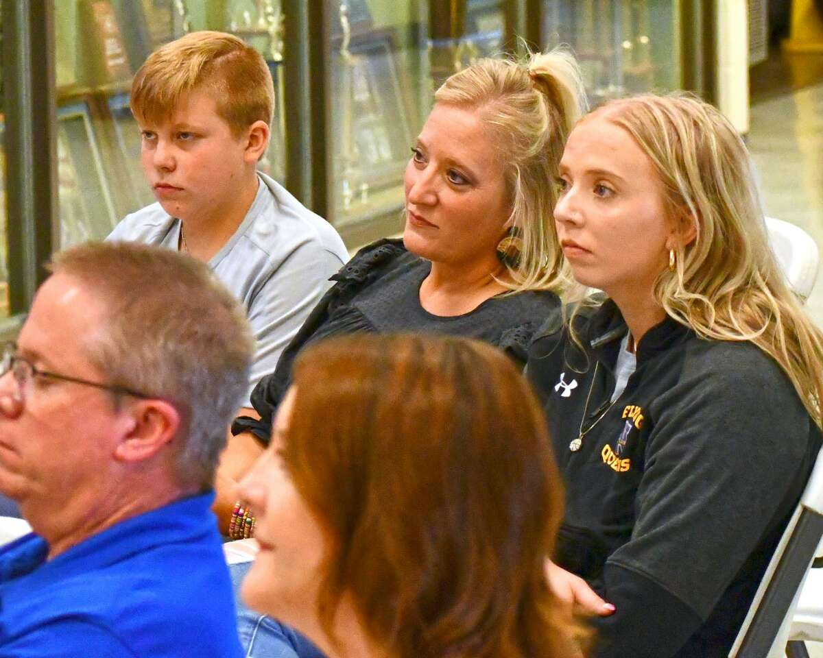 Cooper's family -- son Johnathan (left), wife Amanda (middle), and daughter and current Flying Queens Jenna -- look on during Jason's speech.