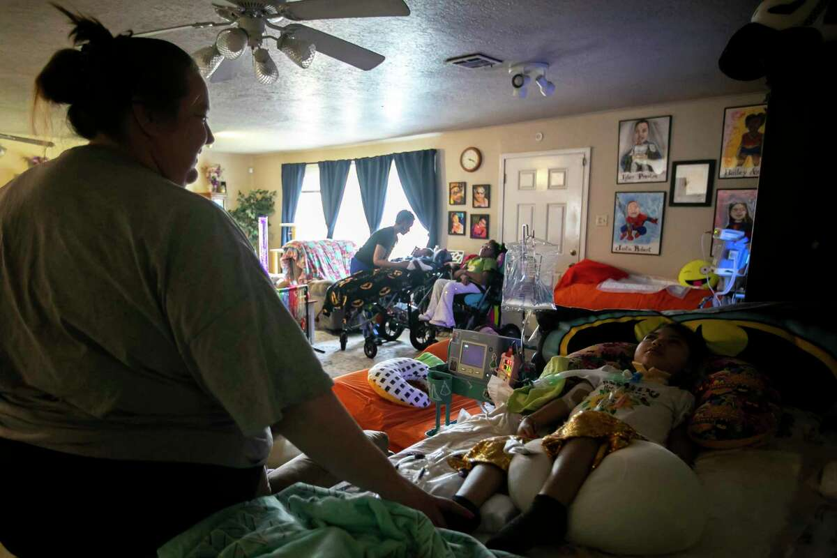 Caroline Cheevers, left, stands next to her youngest daughter, Ava, right, in the Cheevers's Willowbend home on Thursday, June 17, 2021. Caroline and her husband, Stan, have four children who require daily help and are dependent on many machines.