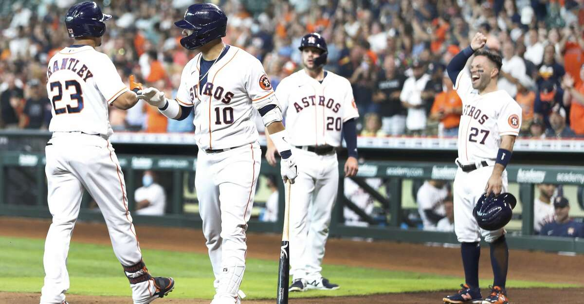 Houston Astros Michael Brantley (23) celebrates his three-run home run with Yuli Gurriel (10) and Jose Altuve (27) during the first inning of an MLB baseball game at Minute Maid Park, Thursday, June 17, 2021.