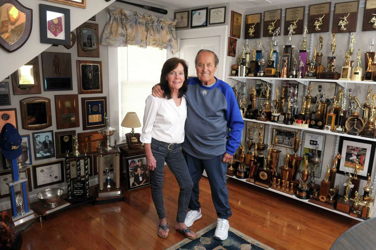 """Former University of New Haven baseball coach Frank """"Porky"""" Vieira and his wife Laura pose in the trophy room of their home in West Haven."""