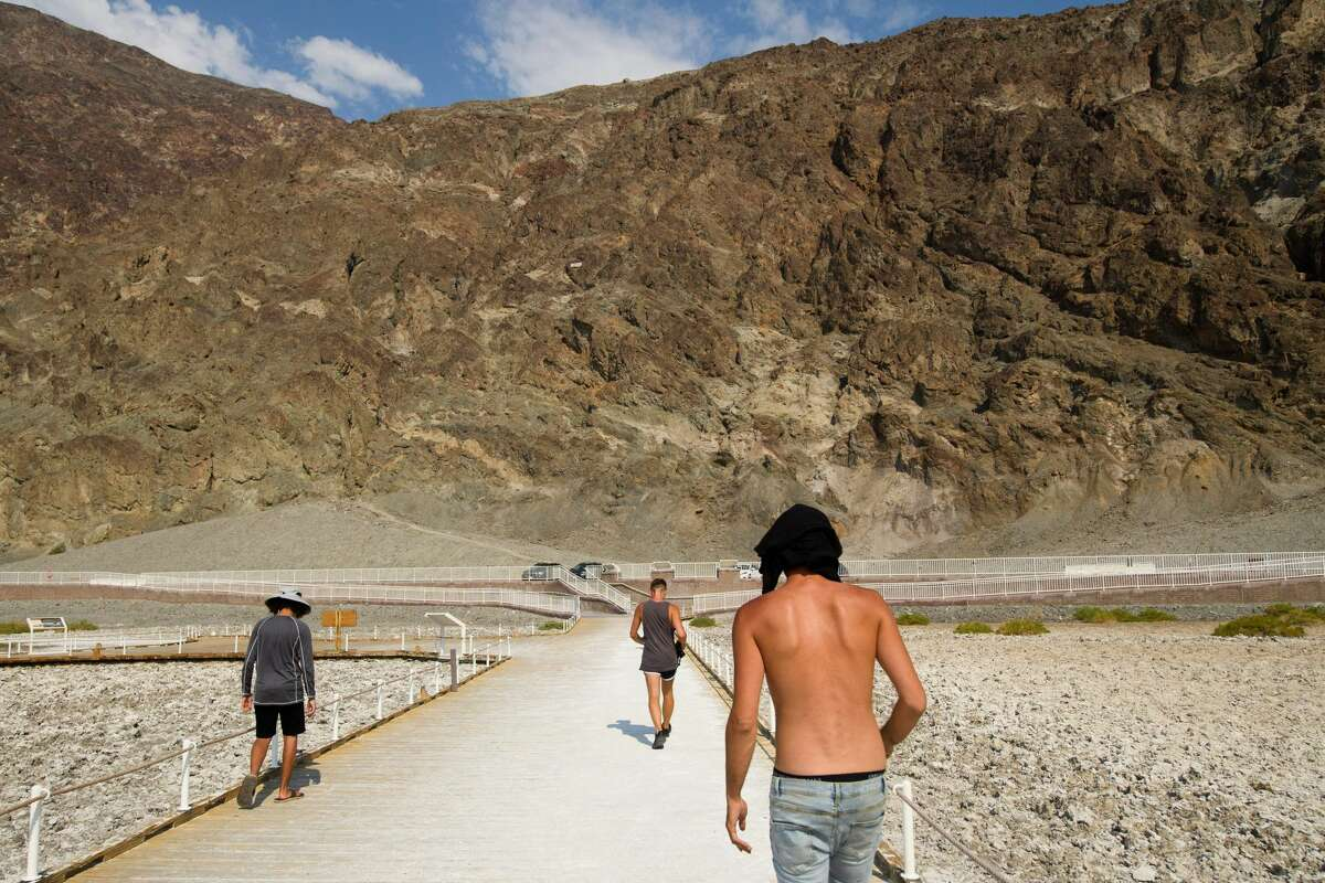 Visitors walk by the salt flats of Badwater Basin inside Death Valley National Park on June 17, 2021 in Inyo County, Calif.