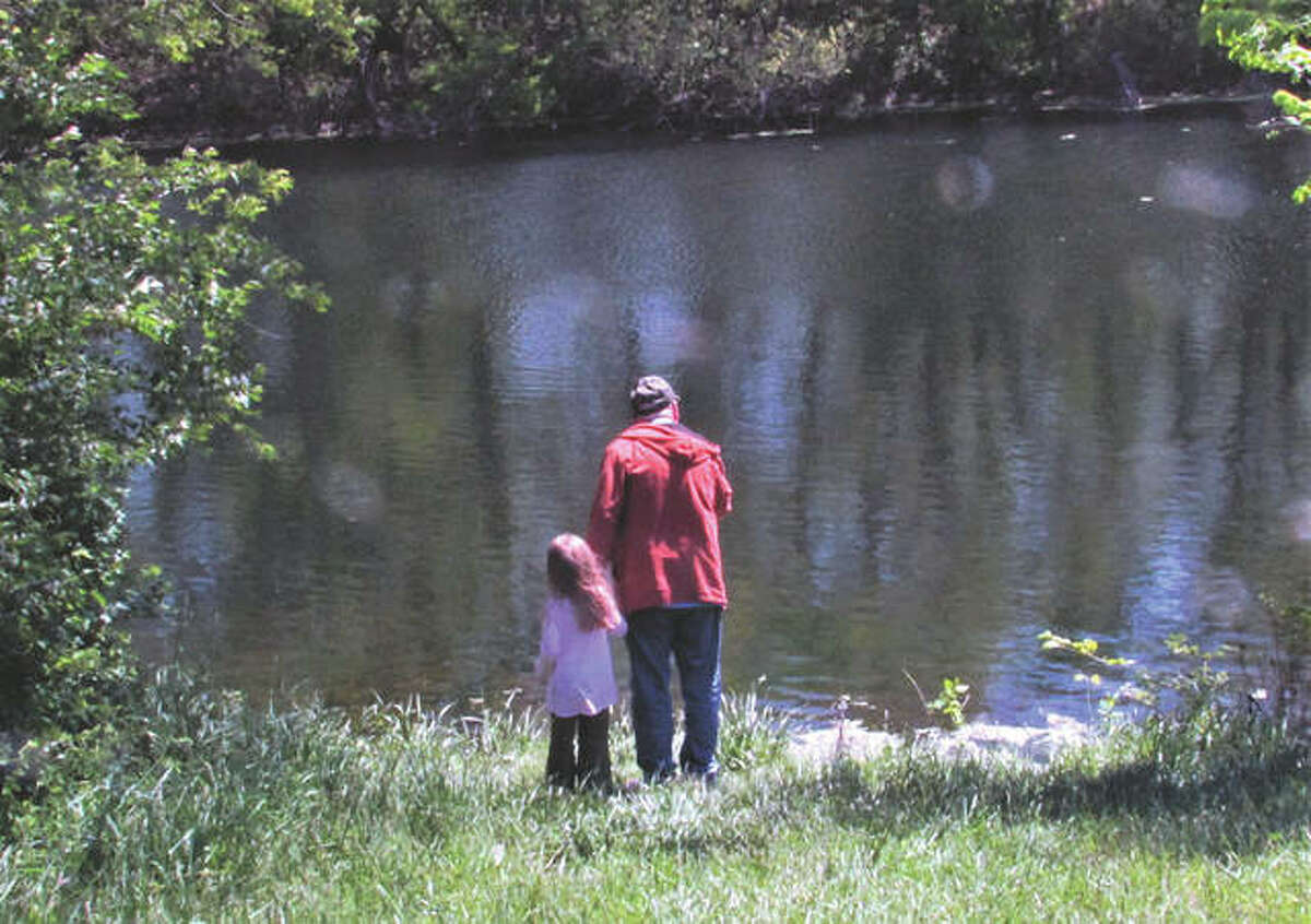 A grandfather and his granddaughter look over the still waters at the reservoir north of Murrayville.